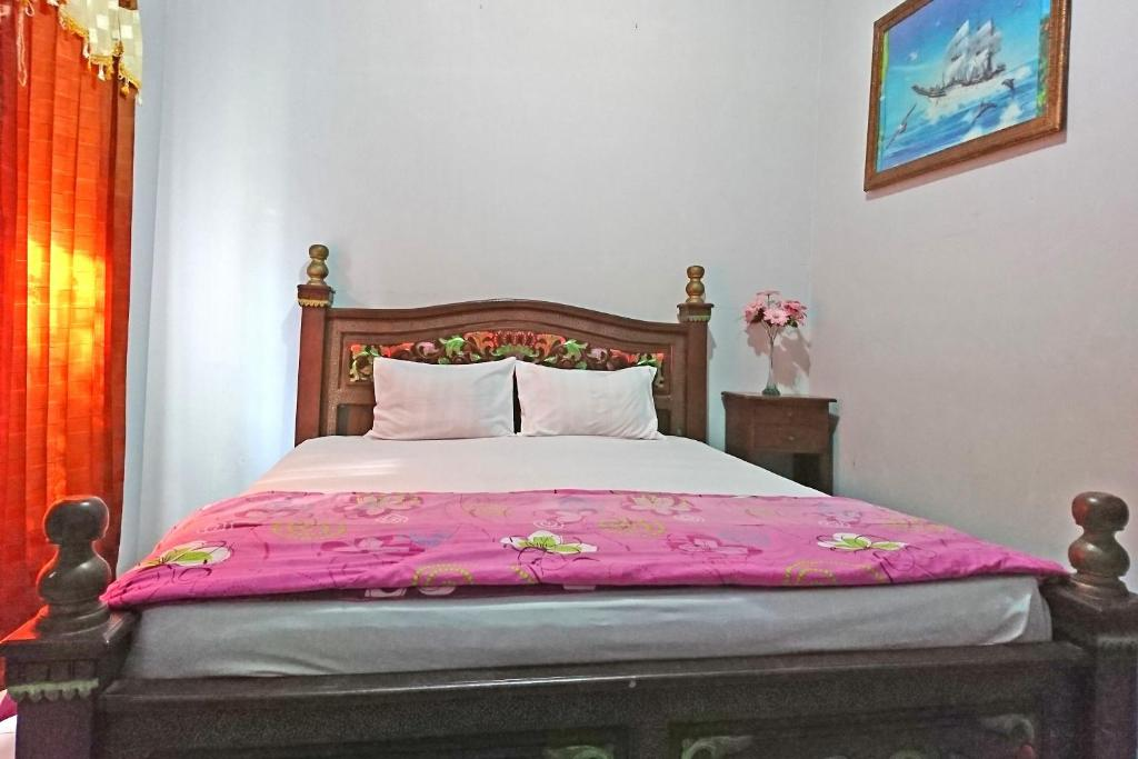 A bed or beds in a room at OYO 2496 Puri Karimun