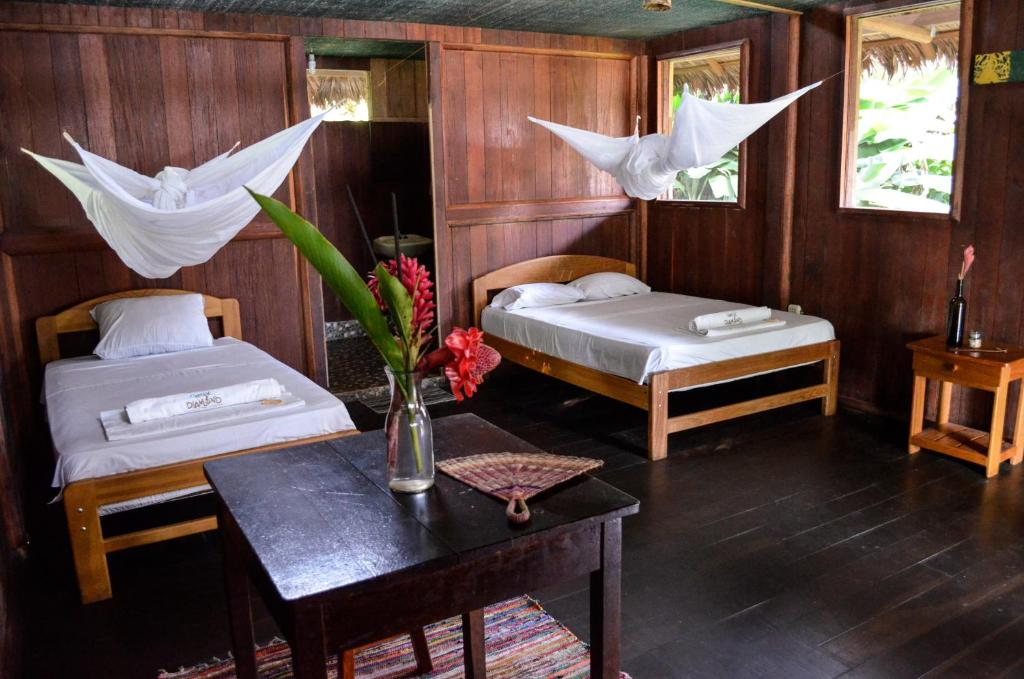 A bed or beds in a room at Green Diamond Amazon Lodge