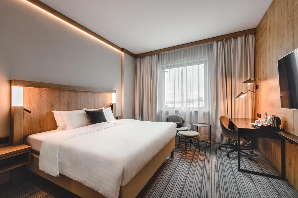 A bed or beds in a room at Courtyard by Marriott Warsaw Airport