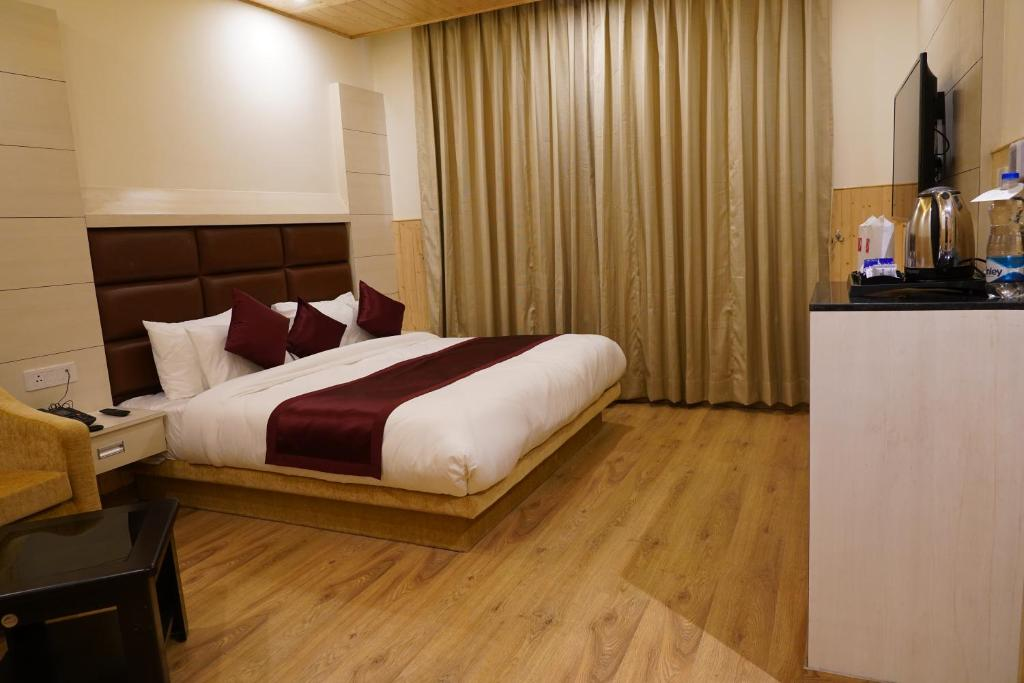 A bed or beds in a room at The Grand Welcome Hotel & Spa