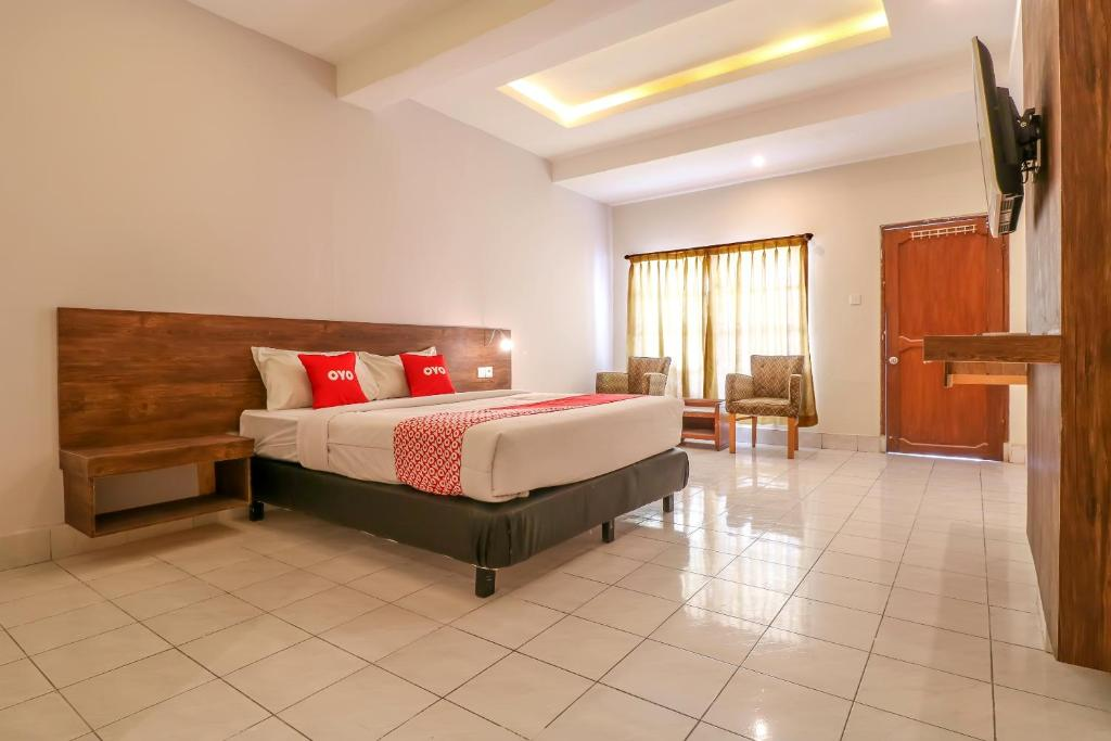 A bed or beds in a room at OYO 1384 Pulau Bali Hotel