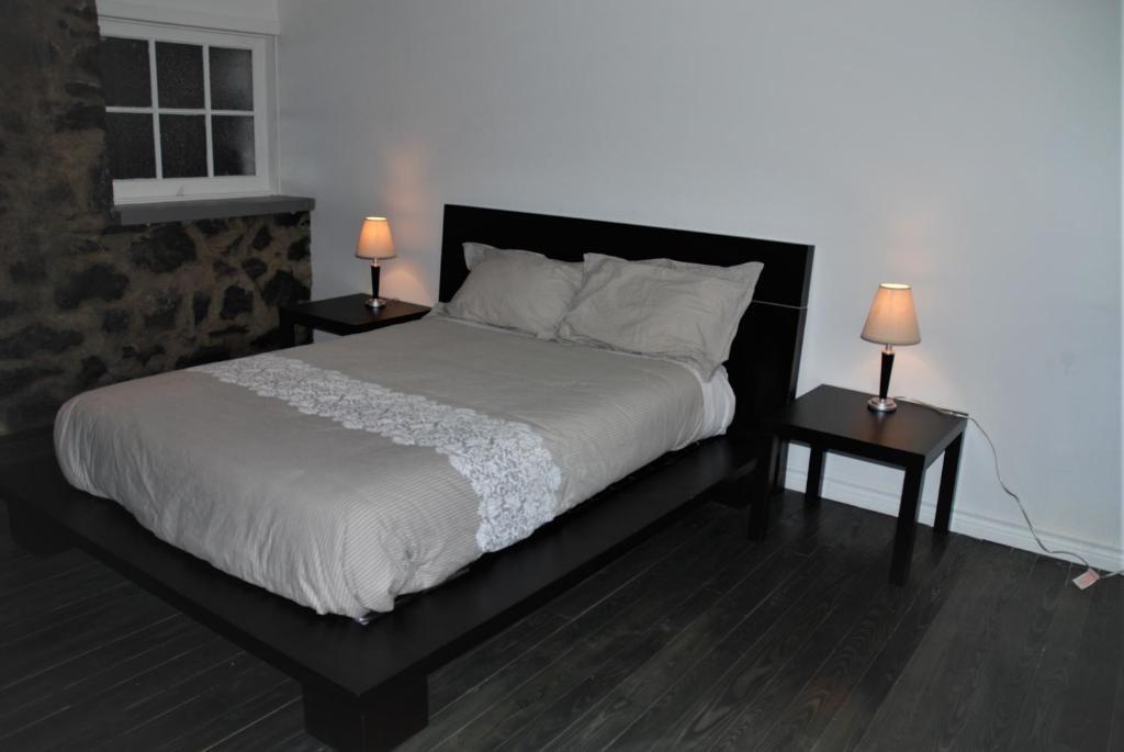 Un ou plusieurs lits dans un hébergement de l'établissement Condo du Manoir du Rocher