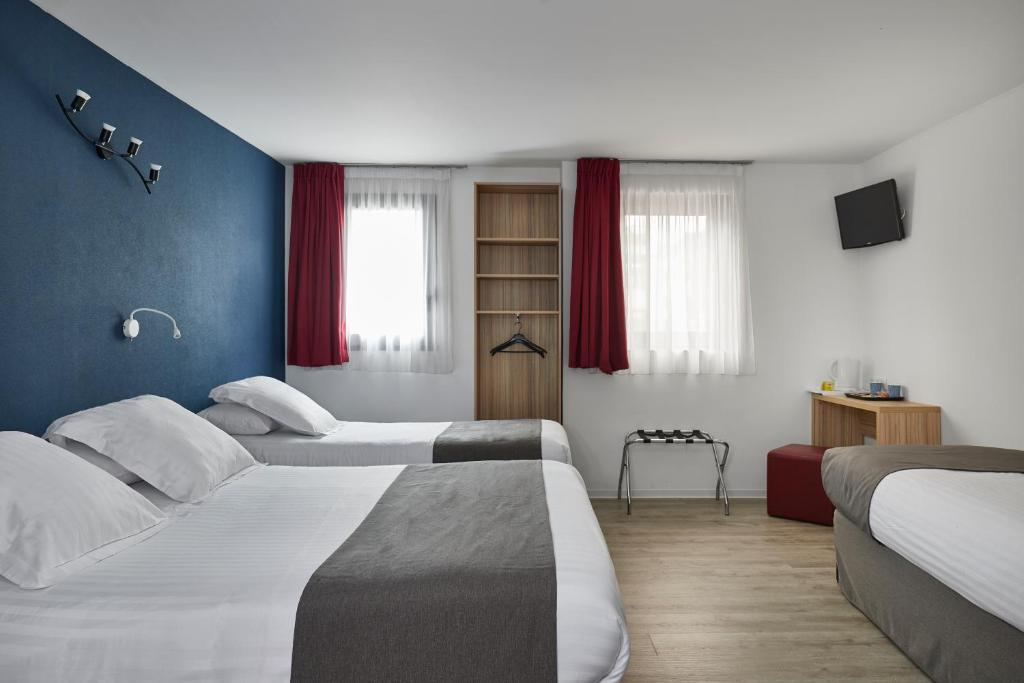 A bed or beds in a room at Kyriad Nice - Stade