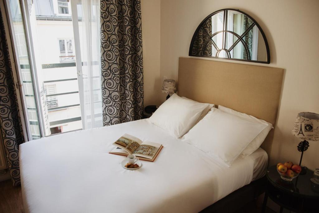 A bed or beds in a room at Arcadie Montparnasse
