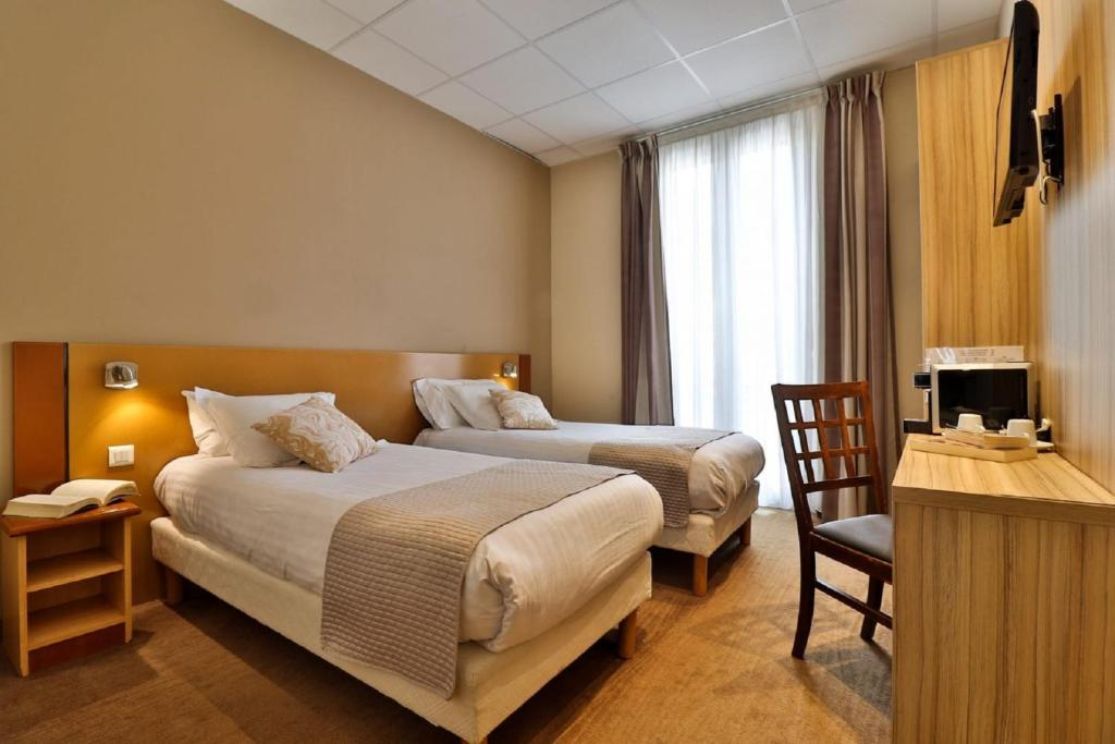 A bed or beds in a room at Kyriad Nice Gare