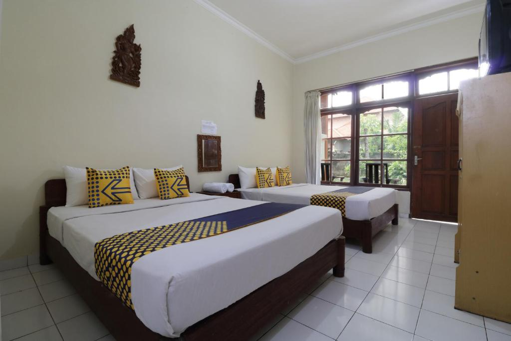 A bed or beds in a room at SPOT ON 2426 Hotel Aget Jaya Ii
