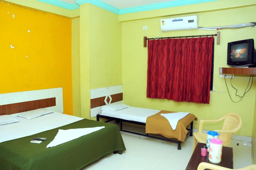 A bed or beds in a room at Hotel Sai Darshan