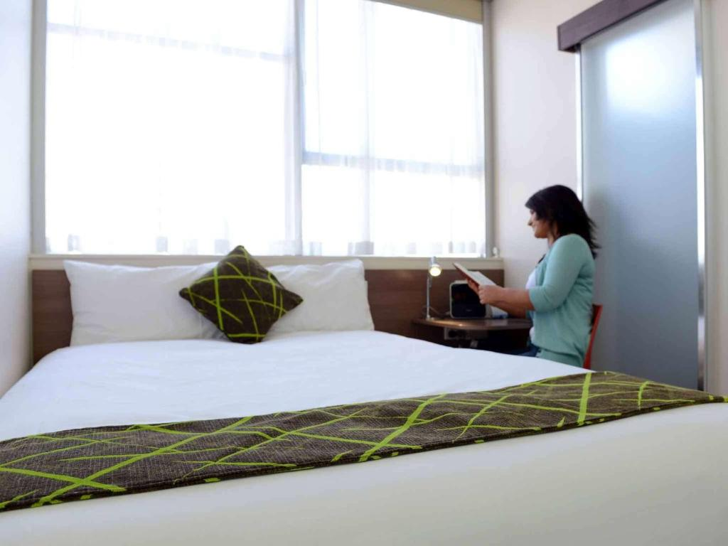 A bed or beds in a room at Ibis Styles Adelaide Grosvenor