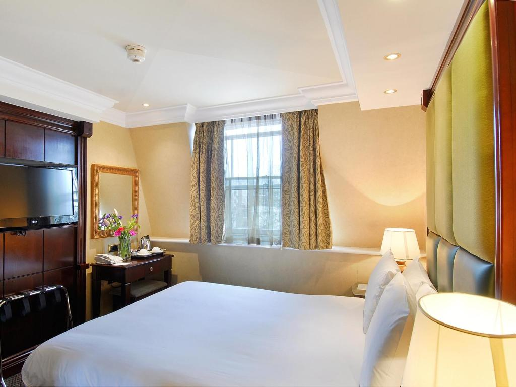 A bed or beds in a room at Hyde Park International - Member of Park Grand London