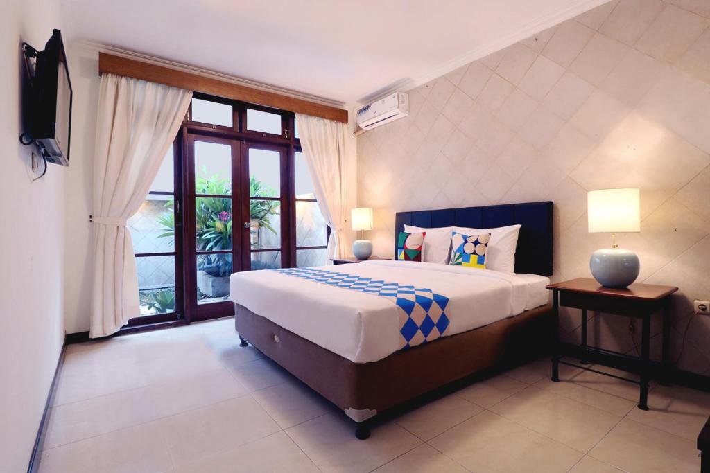 A bed or beds in a room at OYO 2540 Kuta Family B14