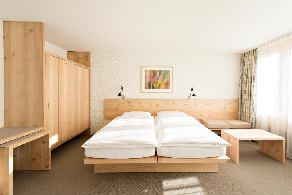 A bed or beds in a room at Hauser Swiss Quality Hotel
