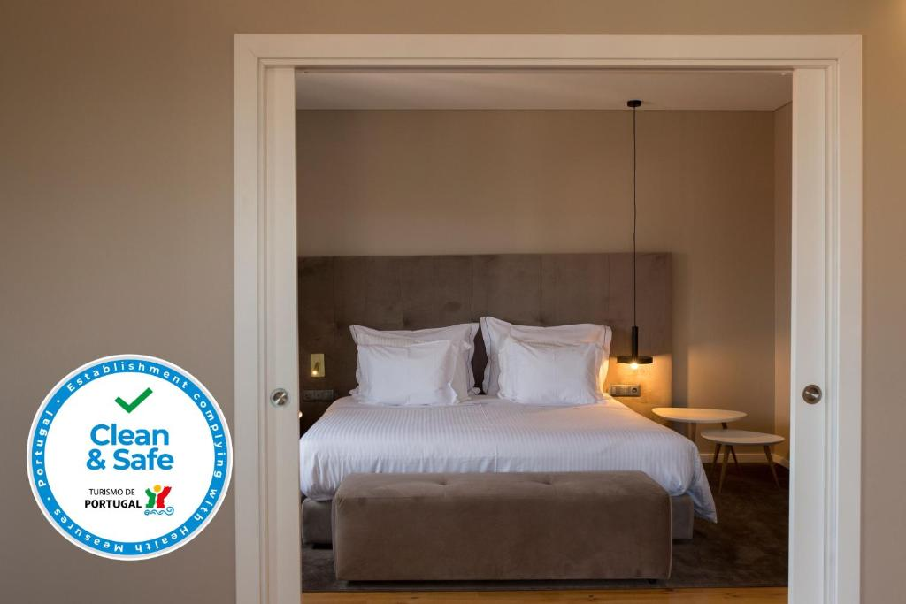 A bed or beds in a room at Avenida Boutique Hotel
