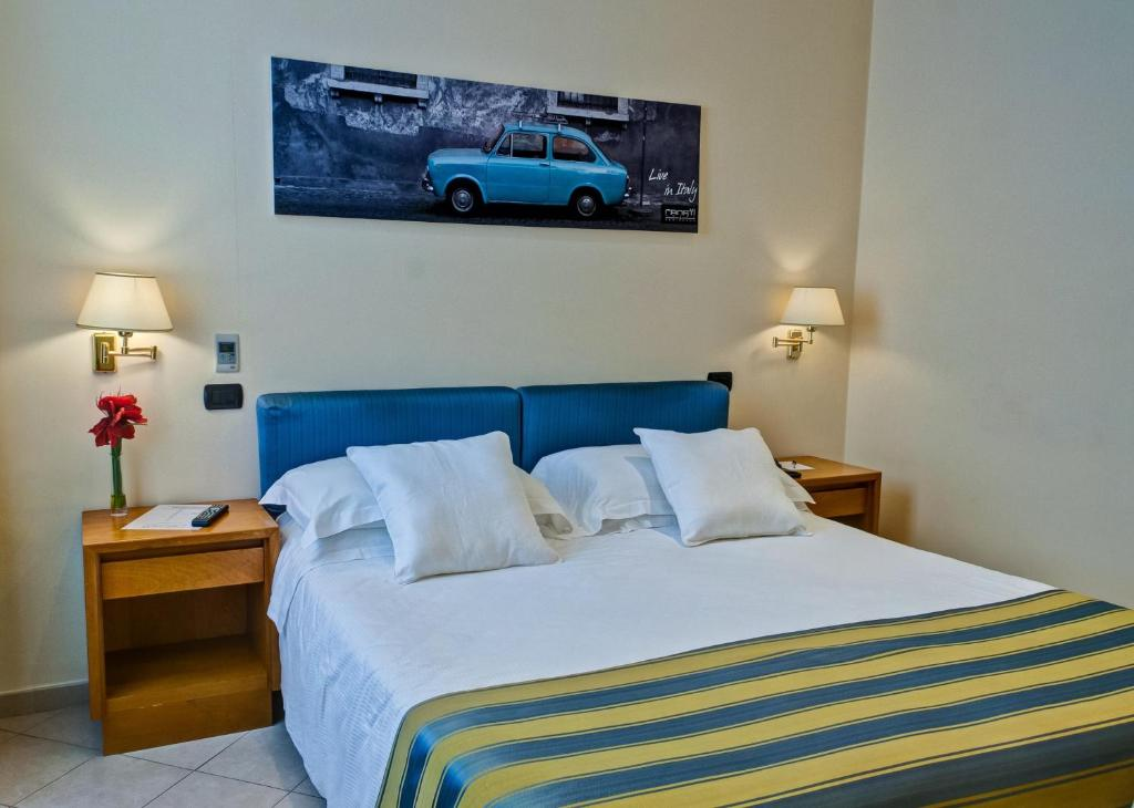 A bed or beds in a room at Crosti Hotel & Residence