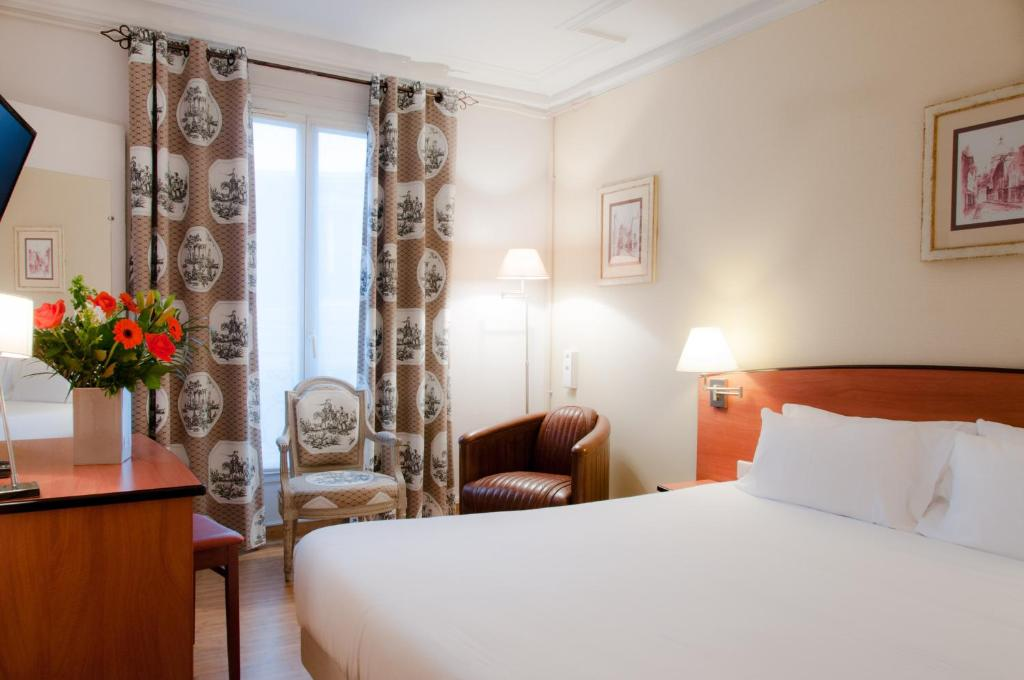 A bed or beds in a room at Hotel Eden Montmartre