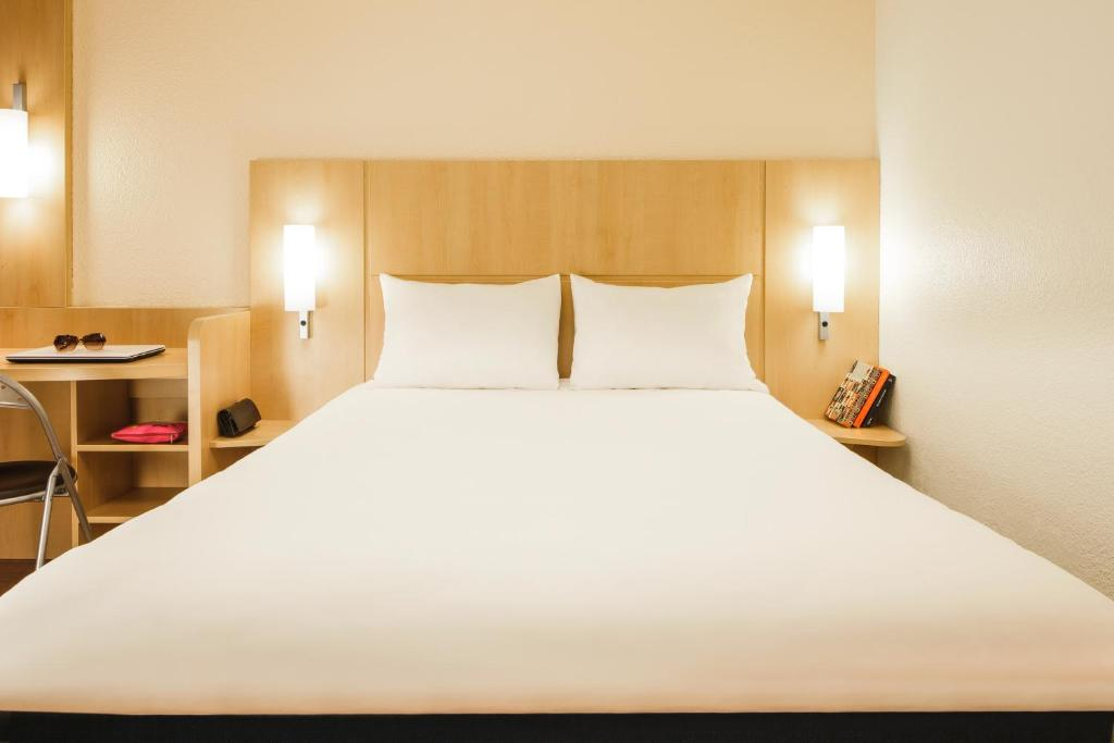 A bed or beds in a room at ibis Versailles Château