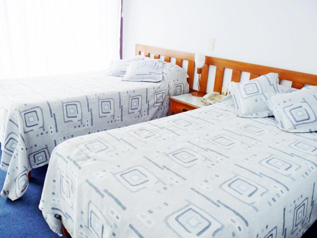 Una cama o camas en una habitación de Hotel los Nogales