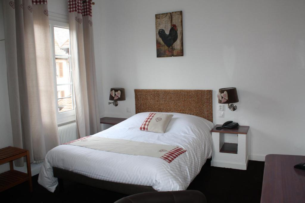 A bed or beds in a room at A la Maison Rouge Hôtel & Restaurant