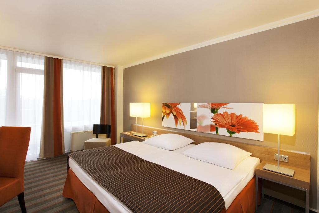 A bed or beds in a room at H4 Hotel Frankfurt Messe