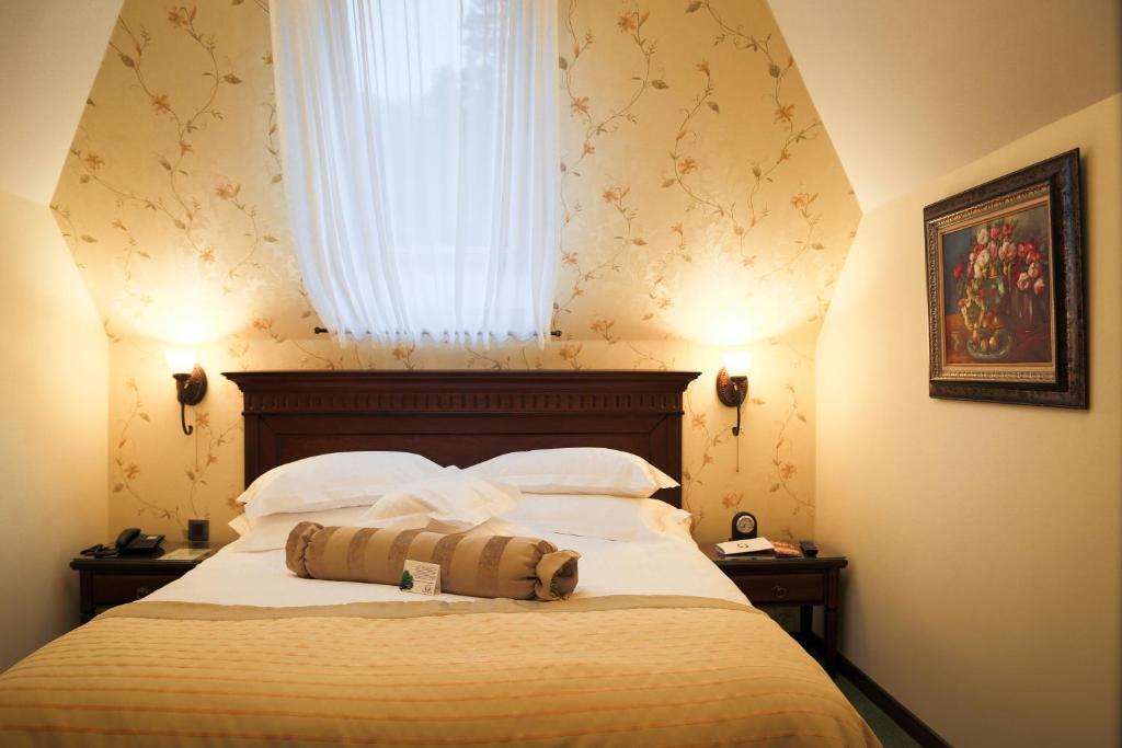 מיטה או מיטות בחדר ב-Hotel Foisorul cu Flori