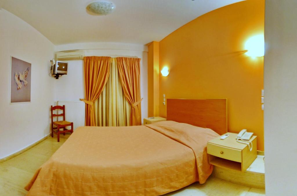 A bed or beds in a room at Aretousa Hotel