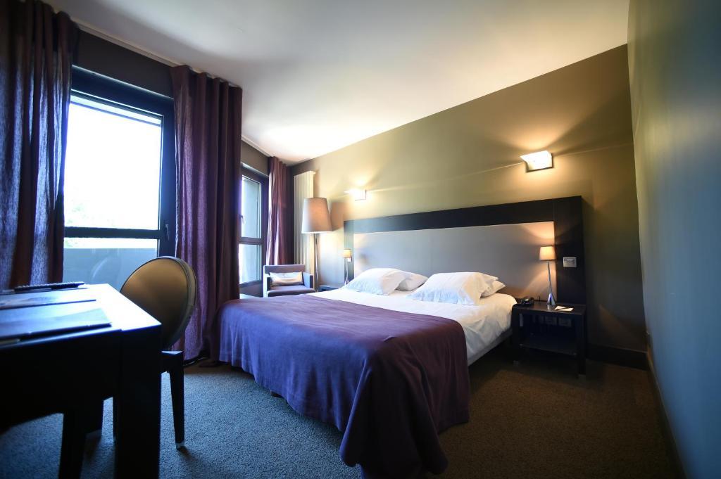 Un ou plusieurs lits dans un hébergement de l'établissement Hôtel Les Rives