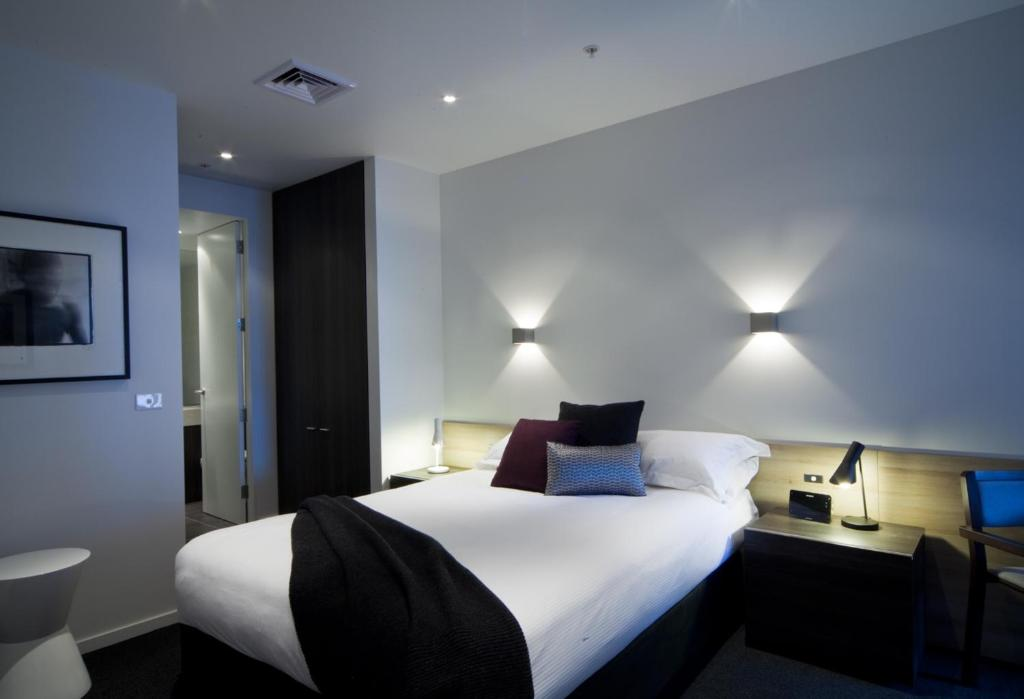 A bed or beds in a room at Tyrian Serviced Apartments Fitzroy