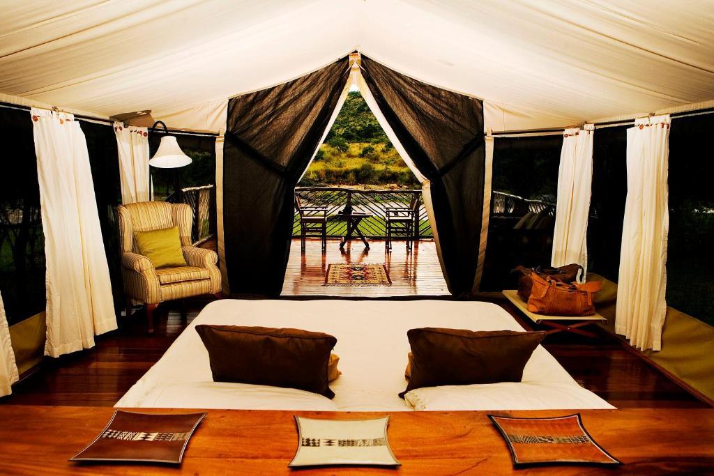 A bed or beds in a room at Karen Blixen Camp Masai Mara