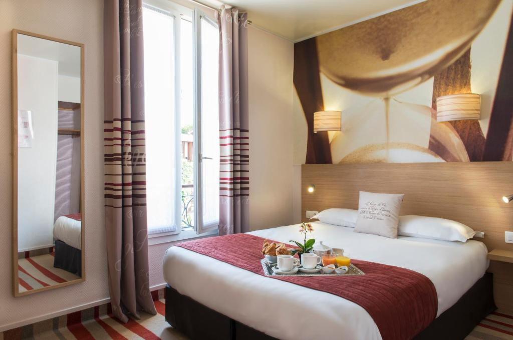A bed or beds in a room at Hotel Ariane Montparnasse by Patrick Hayat