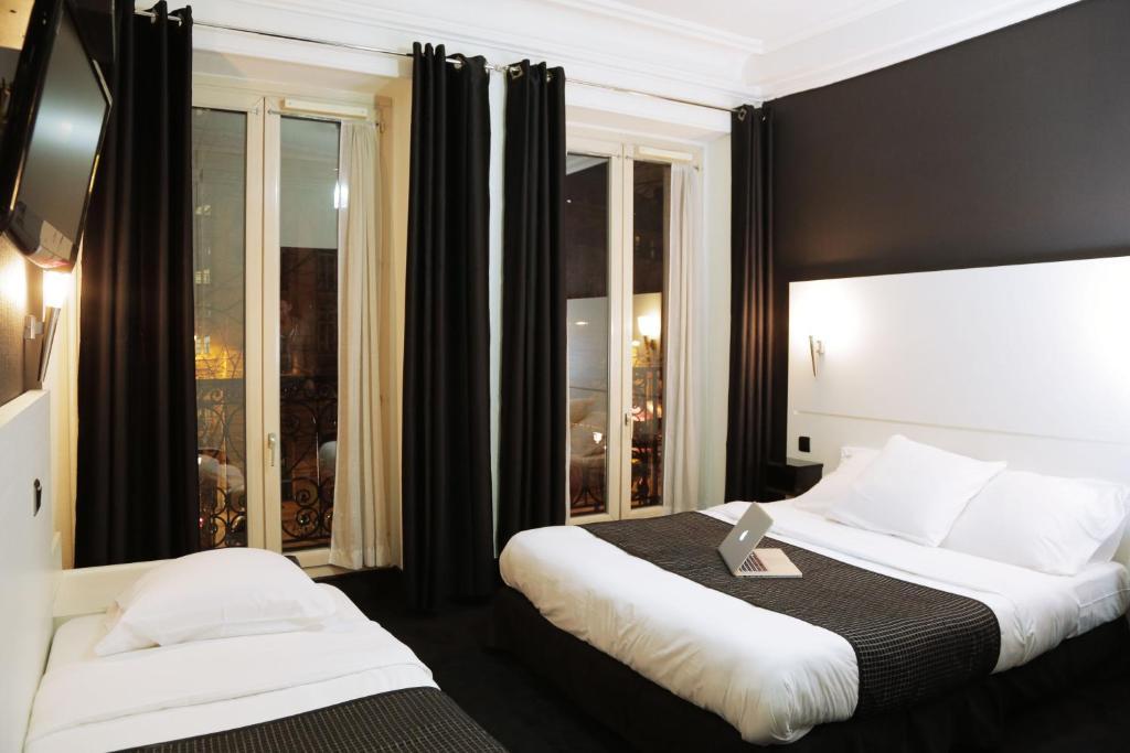 A bed or beds in a room at Hôtel de l'Exposition - République