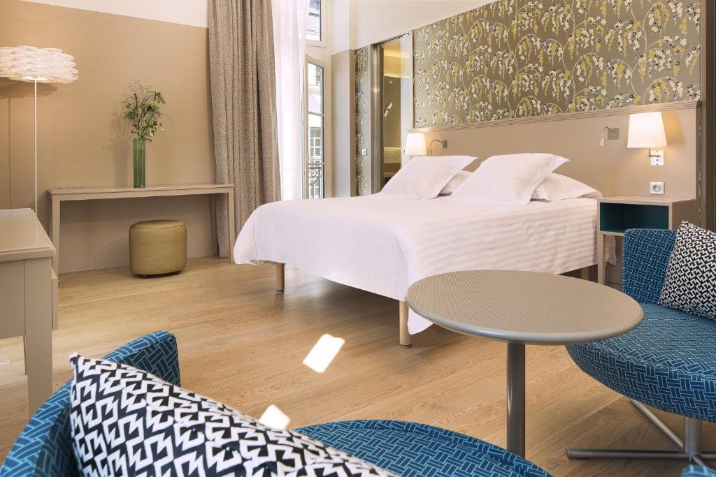 A bed or beds in a room at Oceania l'Hôtel de France Nantes