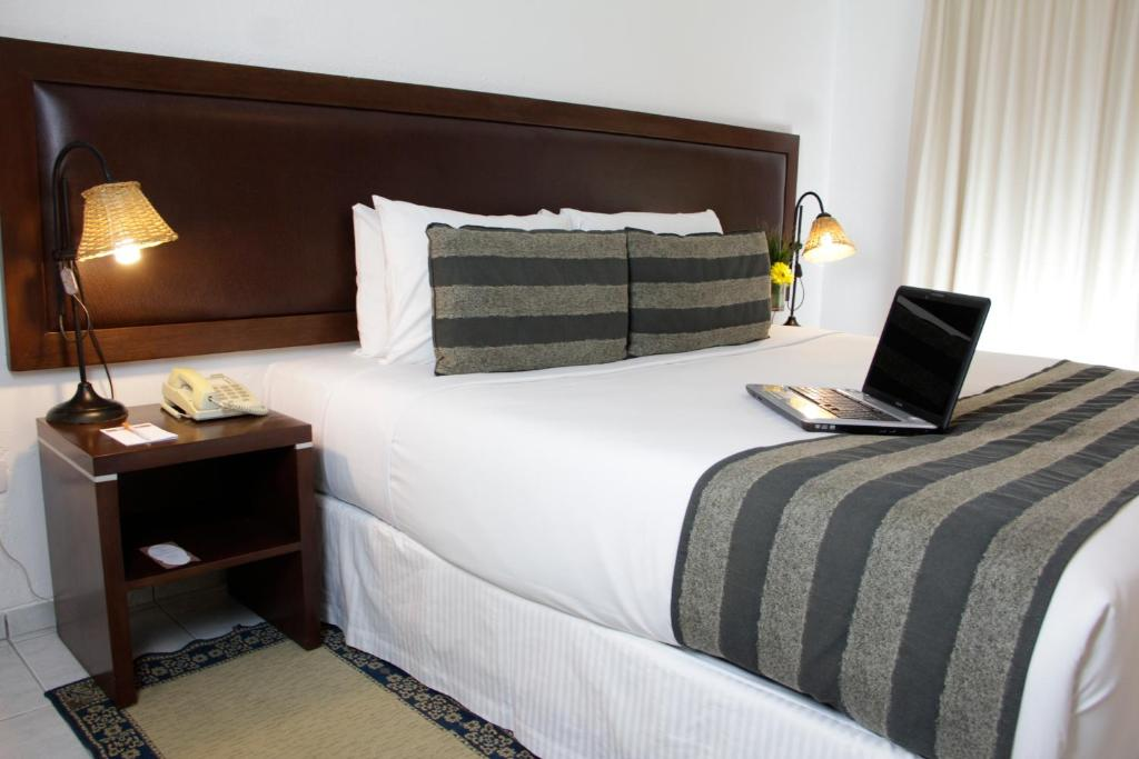 A bed or beds in a room at Buganvillas Hotel Suites & Spa