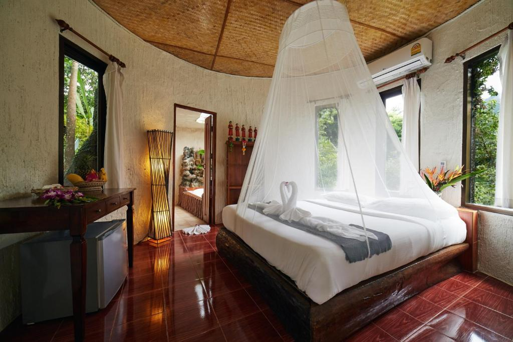 A bed or beds in a room at Khao Sok Paradise Resort