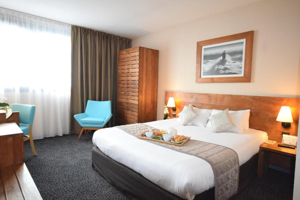 A bed or beds in a room at Kyriad Prestige Bordeaux Aeroport