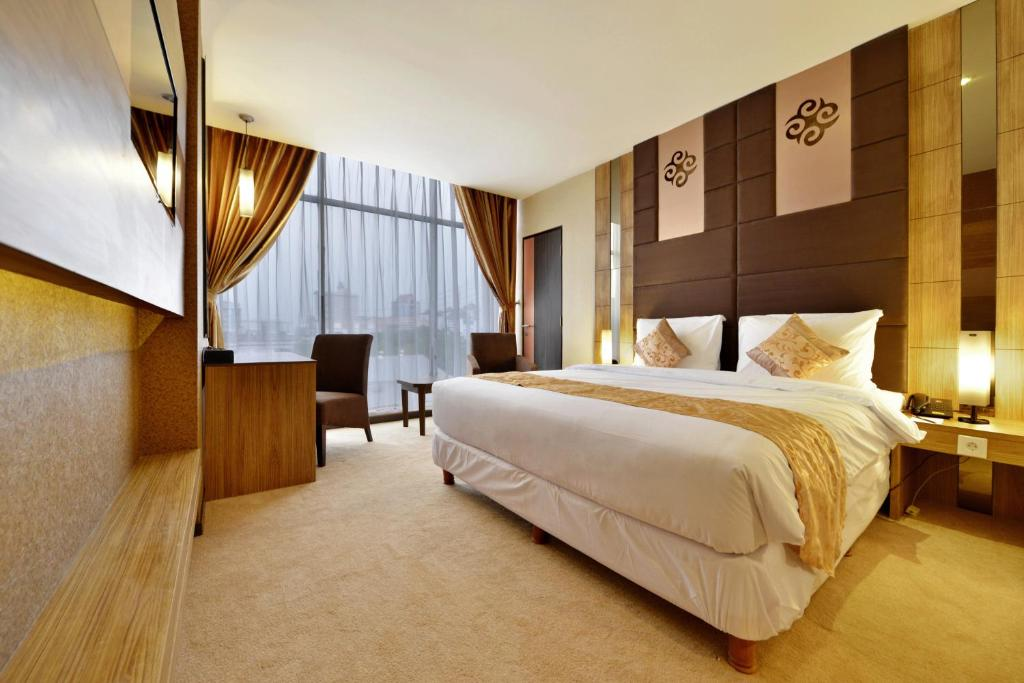 A bed or beds in a room at Grand Tjokro Jakarta