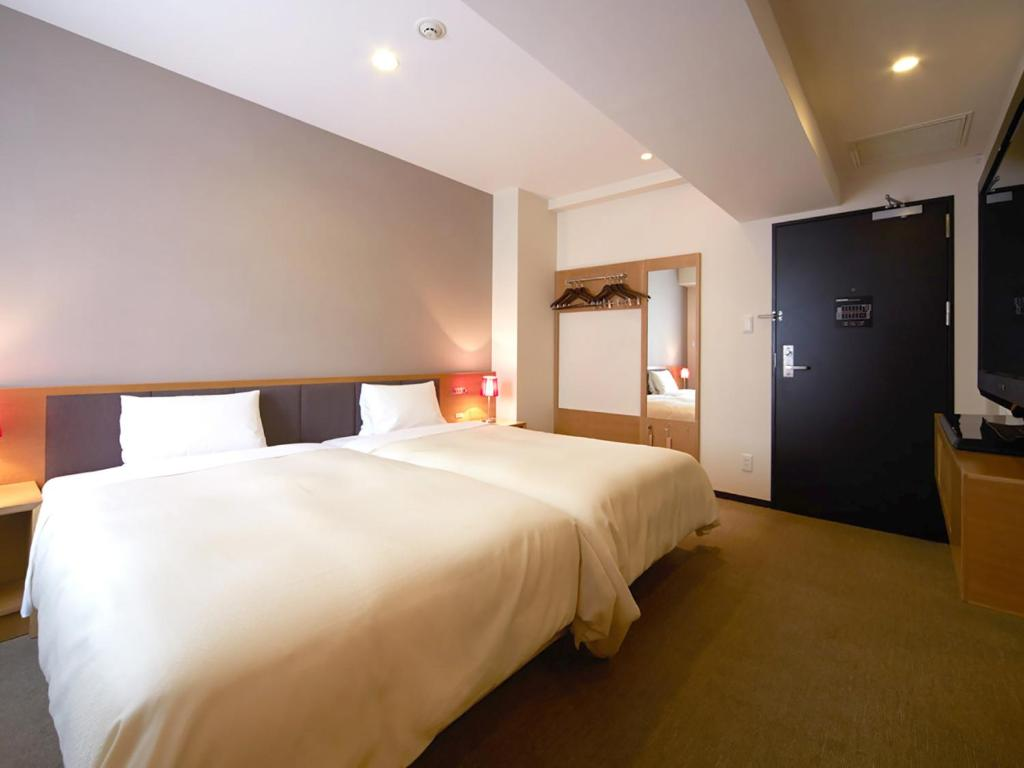 A bed or beds in a room at Vessel Inn Hakata Nakasu