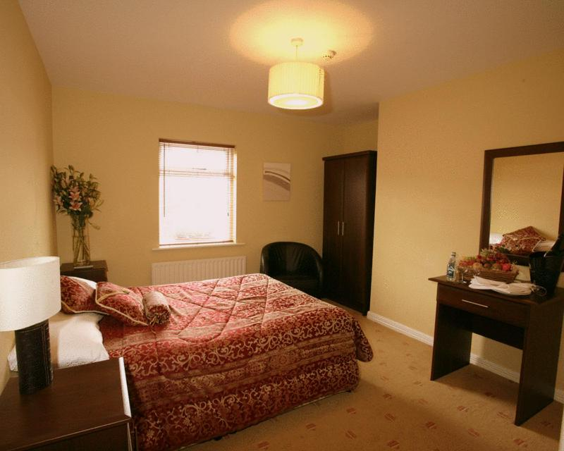 A bed or beds in a room at The Mayfly Hotel