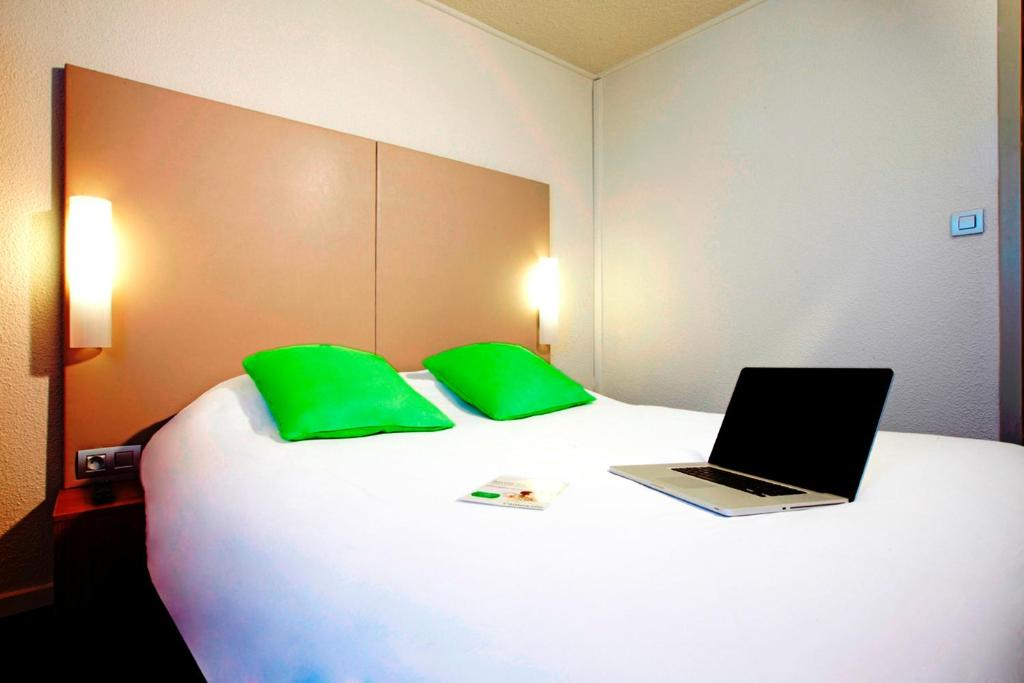 A bed or beds in a room at Campanile Paris Ouest - Gennevilliers Barbanniers