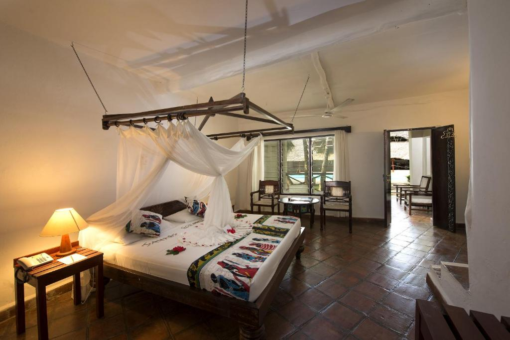 A bed or beds in a room at Sandies Tropical Village