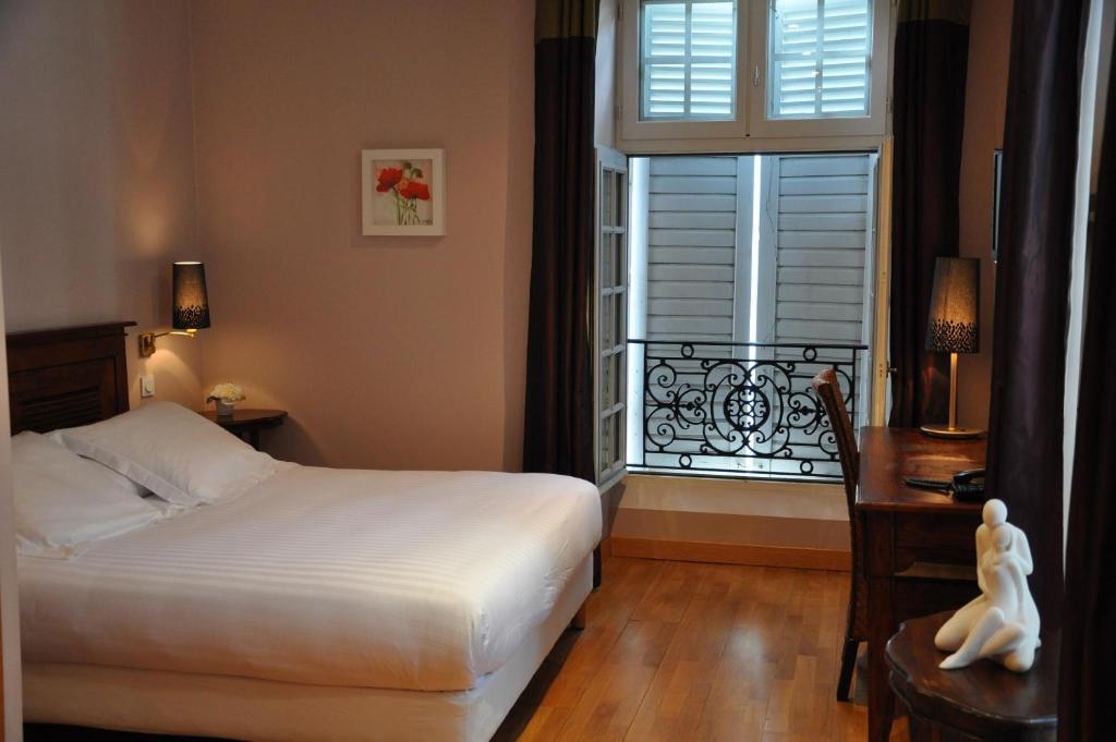 A bed or beds in a room at The Originals City, Hôtel La Reine Jeanne, Orthez (Inter-Hotel)