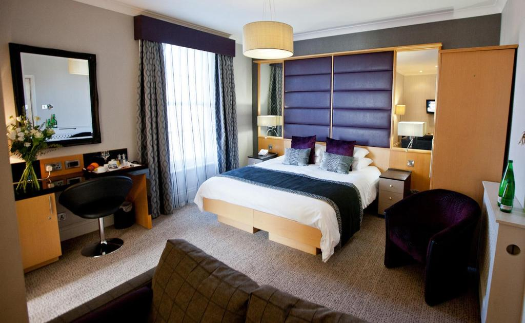 A bed or beds in a room at New Northumbria Hotel