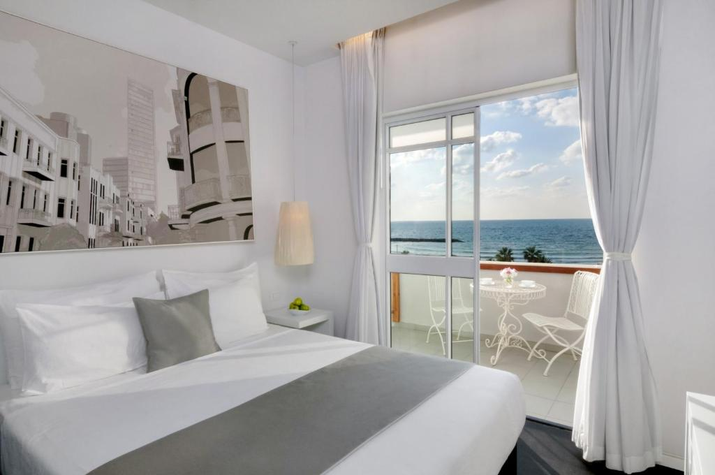A bed or beds in a room at Rimonim By The Beach