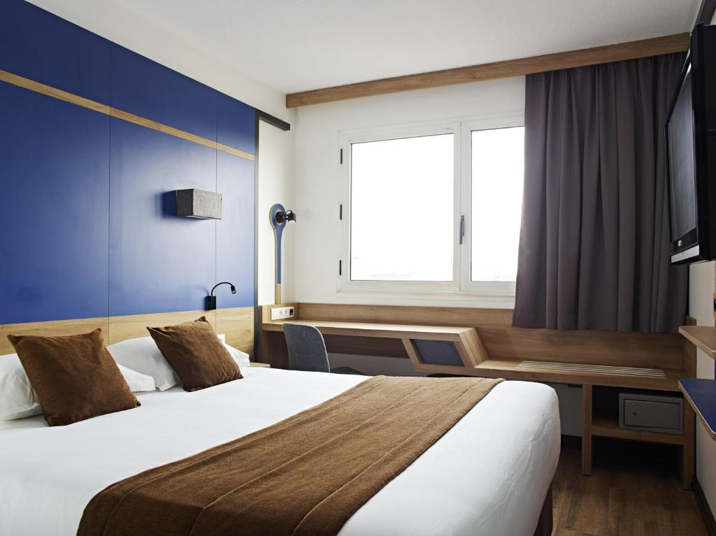 A bed or beds in a room at Median Paris Congrès