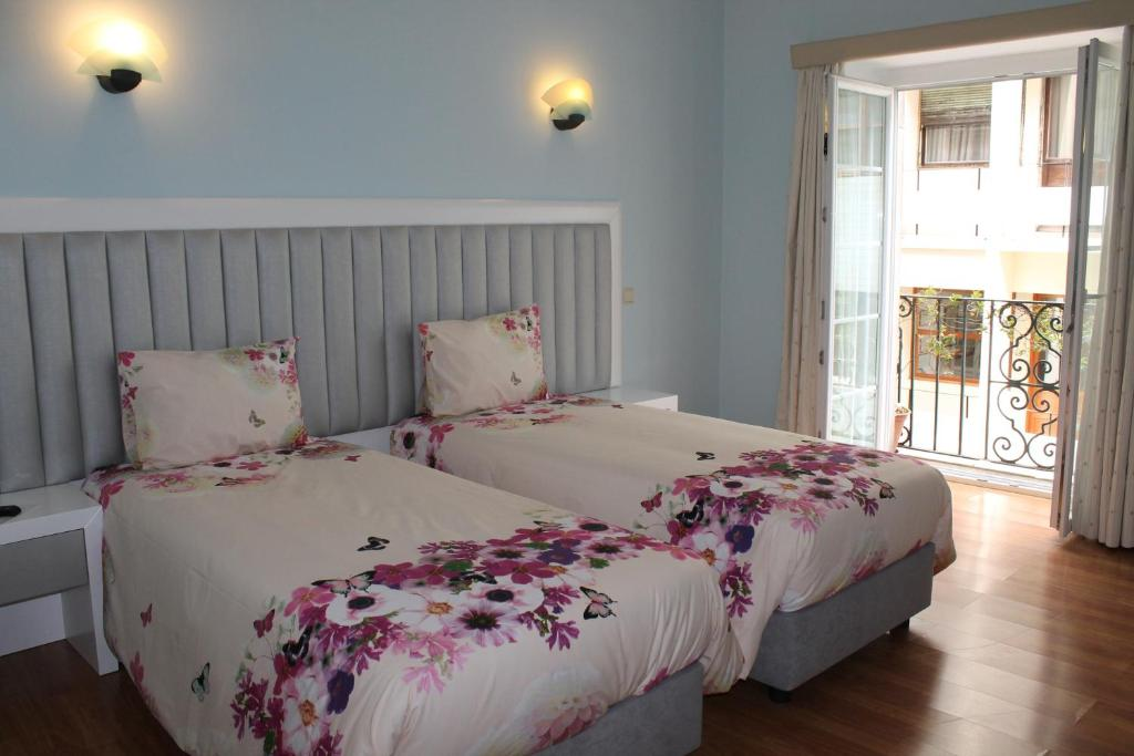 A bed or beds in a room at Grande Oceano Guest House