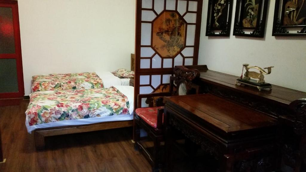 A bed or beds in a room at Tiananmen Best Year Courtyard Hotel