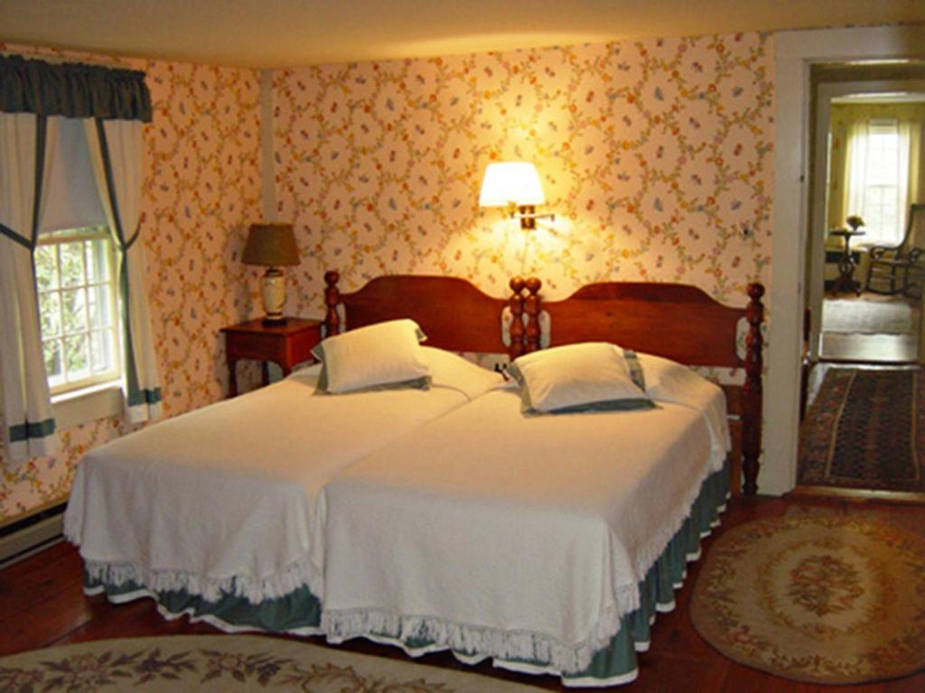 A bed or beds in a room at The Inn at Woodchuck Hill Farm