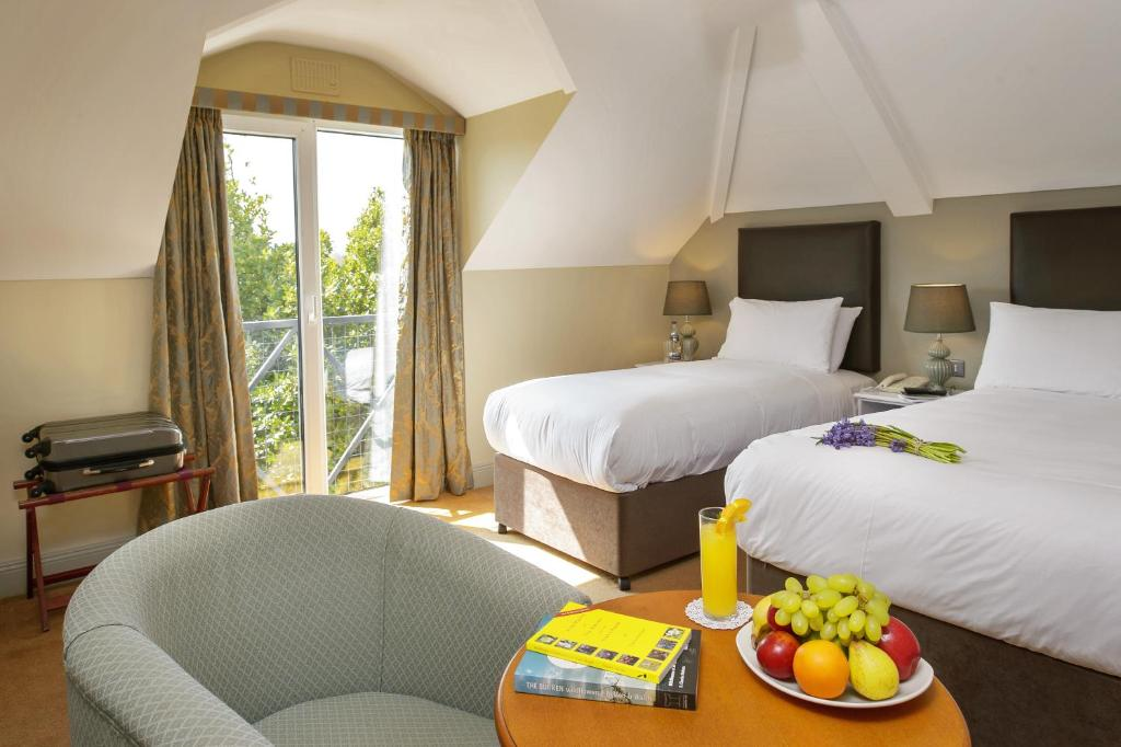 A bed or beds in a room at Hylands Burren Hotel