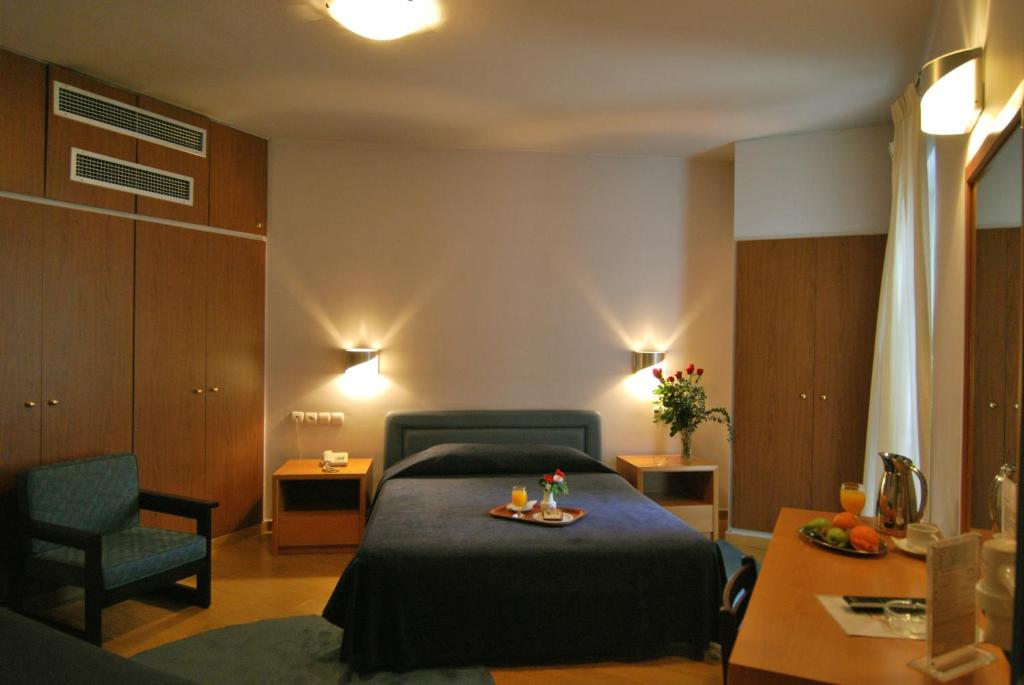 A bed or beds in a room at Iniohos Hotel