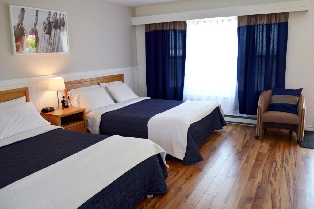 A bed or beds in a room at Condo & Motel des Berges