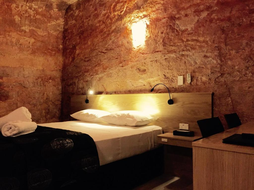 A bed or beds in a room at The Lookout Cave Underground Motel