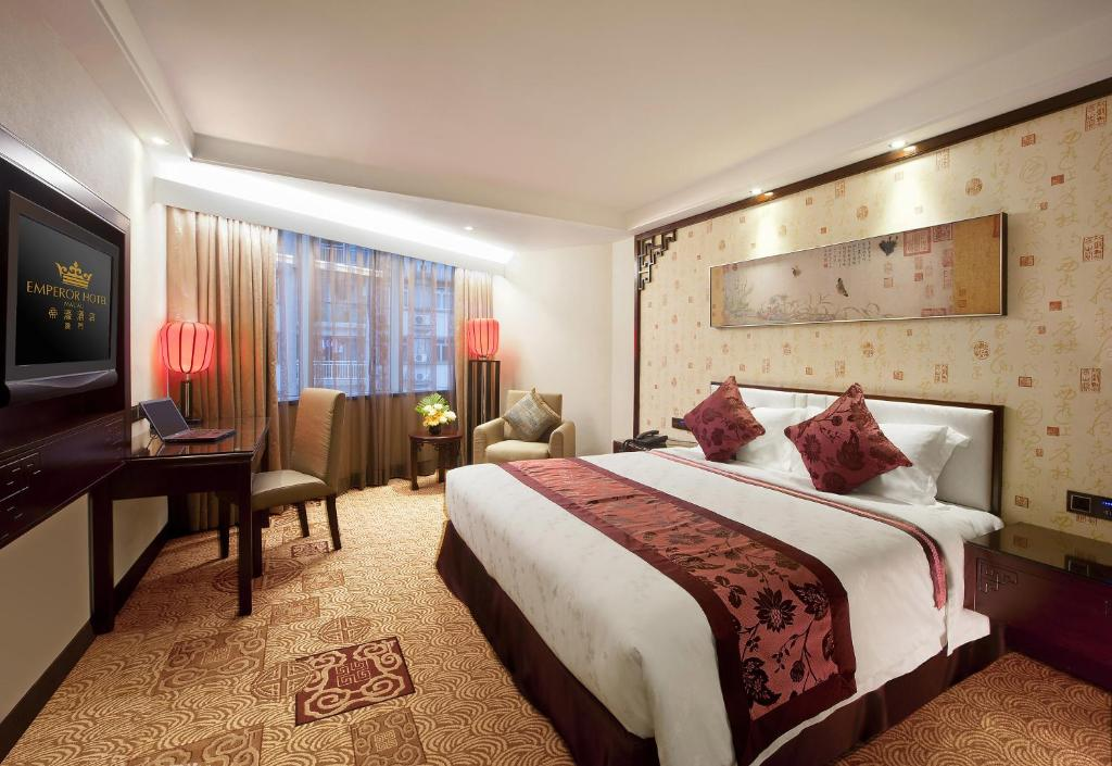 A bed or beds in a room at Emperor Hotel